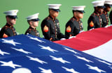 United States Marines hold a giant American Flag across the court at the U.S. Open.