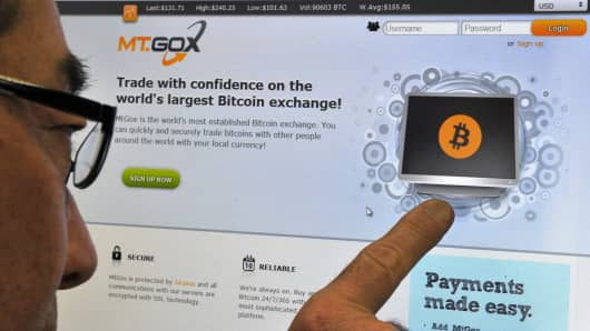 This photo illustration shows a man looking at the bitcoin exchange website of Mt. Gox in Tokyo last February.