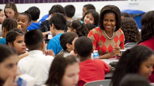 First Lady Michelle Obama eats lunch with school children in the cafeteria at Parklawn Elementary School in Alexandria, Virginia, January 25, 2012.