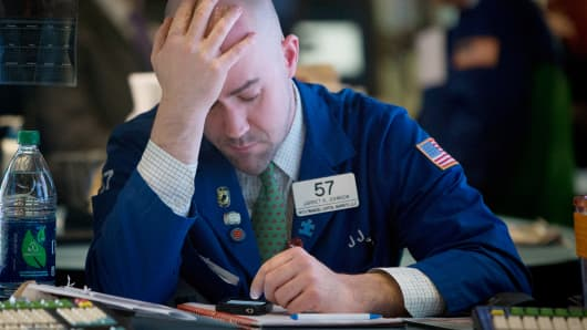 A trader holds his head in his hand on the floor of the New York Stock Exchange (NYSE) in New York.