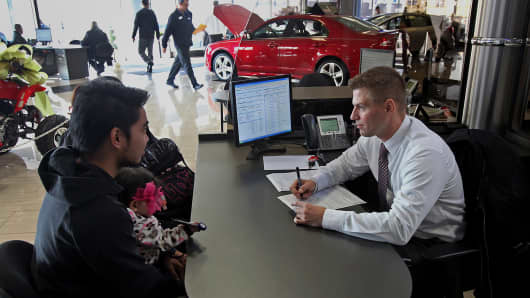 A sales representative assists customers at Golf Mill Ford car dealership in Niles, Ill.