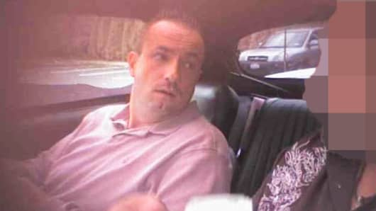 In this undercover video still Dejvid Mirkovic, left, hands over money to an undercover agent posing as a hit man.