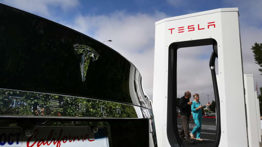 A Model S is parked in front of a new Tesla Supercharger outside the Tesla factory in Fremont, Calif.