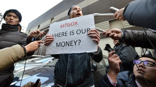 A bitcoin trader is surrounded by reporters as he protests against Tokyo-based bitcoin changer Mt.Gox in front of the company's office.