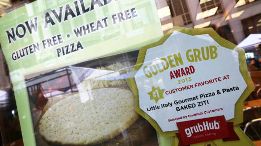 In this Aug. 10, 2013, file photo, a GrubHub sticker is displayed next to photographs of items on the menu in the window of a restaurant in New York's Times Square.