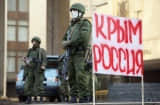 "Soldiers guard the Crimean parliament in Simferopol next to a sign that reads: ""Crimea Russia,""  March 1, 2014."