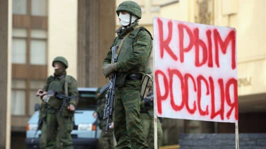 "Soldiers guard the Crimean parliament in Simferopol next to a sign that reads: ""Crimea Russia."""