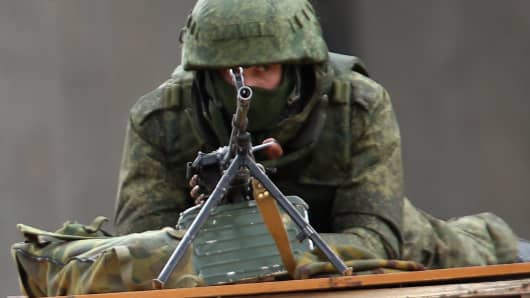 A soldier without identifying insignia mans a machine gun outside the Crimean parliament building shortly after several dozen soldiers took up positions there on March 1, 2014 in Simferopol, Ukraine.