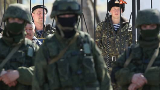 Ukrainian soldiers stand inside a Ukrainian military base as unidentified heavily armed soldiers stand outside, March 3, 2014, in Perevalne, Ukraine.