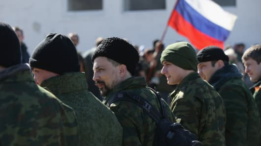 A unit claiming to Cossack and other citizen pro-Russian volunteers arrive to take up position outside a Ukrainian miltary base where heavliy-armed unidentifed soldiers have surrounded Ukrainian soldiers inside as Russian flag flies behind in Crimea on March 3, 2014 in Perevalne, Ukraine.