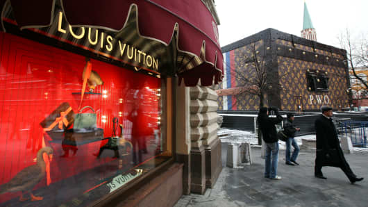 Pedestrians pass a promotional exhibit for Louis Vuitton, a large wooden chest adorned in the trademark pattern and logo of luxury manufacturer LVMH Moet Hennessy Louis Vuitton SA on display next to the GUM shopping mall, left, in Red Square, Moscow, Russia.