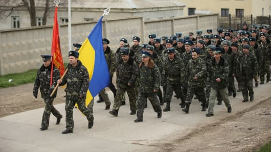 Unarmed Ukrainian troops bearing their regiment and the Ukrainian flags march to confront soldiers under Russian command occupying the Belbek airbase in Crimea on March 4, 2014 in Lubimovka, Ukraine.