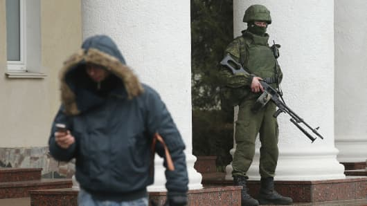 One of approximately 20 soldiers wearing no identifying insignia patrols outside the Simferopol International Airport.