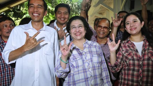 Jakata gubernatorial candidate Joko Widodo (L) poses for a photograph next to former Indonesian president Megawati Sukarnoputri (C) as they vote for governor in Jakarta in September 2012.
