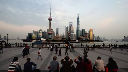 Tourists view the Pudong financial district skyline from the historic Bund in Shanghai.