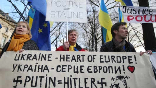 People hold placards Ukrainian flags and a banner during a demonstration to support Ukraine's Pro-European protesters on March 5, 2014 in Paris.