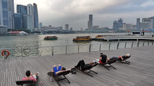 People lying on beach chairs along the Marina Bay promenade in Singapore.