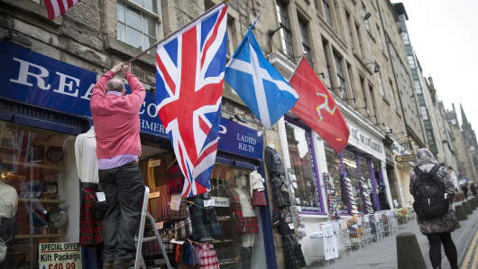 A shopkeeper erects a British Union flag next to Scottish Saltire flag as he prepares the front of his store for business