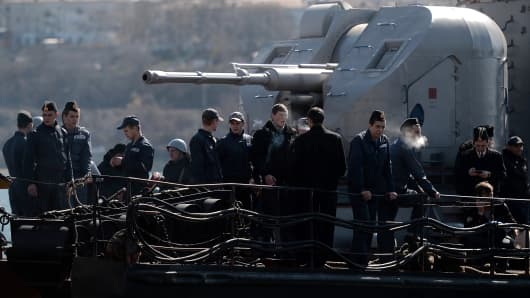Ukrainian soldiers stand guard on board the navy corvette Ternopil as Russian forces patrol nearby in the harbor of the Ukrainian city of Sevastopol on March 5, 2014.