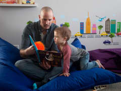 David Juip, a stay-at-home dad for two years, reads to his son Jonah, 3, at their home in Wauconda, Ill.