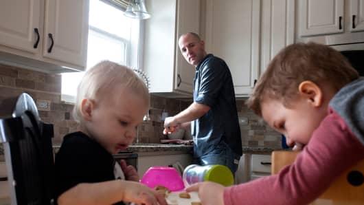 Juip peels oranges for sons Ari, 1, and Jonah.