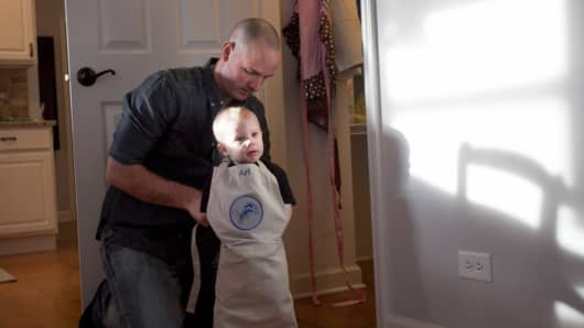 Juip puts an apron on his son Ari while making dinner.