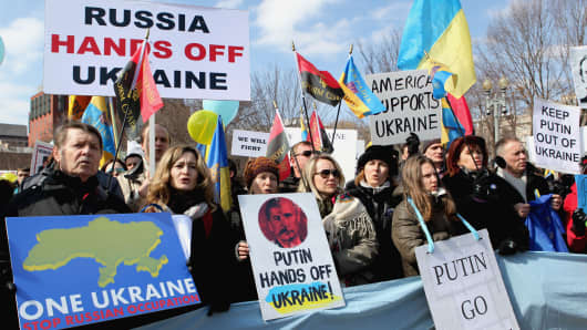 People hold placards and Ukrainian flags during a rally in front of the White House in Washington.