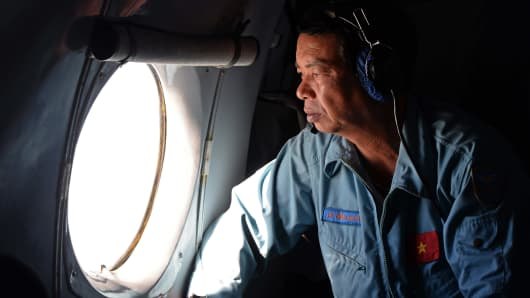 This aerial picture taken from aboard a flying Soviet-made AN-26 used as a search aircraft by Vietnamese Air Force to look for missing Malaysia Airlines flight MH370, shows an Air Force officer looking out a window over the southern seas off Vietnam on March 9, 2014.