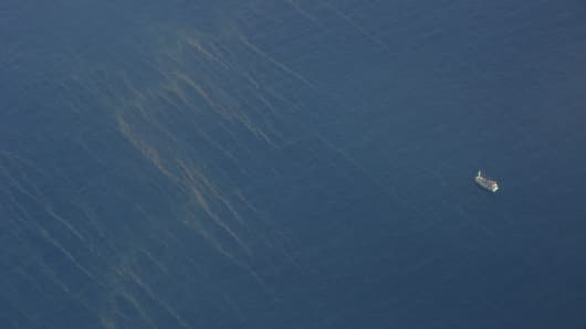 This aerial picture taken from an aircraft used by Vietnamese Air Force to look for missing Malaysia Airlines flight MH370, shows a boat (R) sailing past oil spills (L) on thesouthern seas of Vietnam on March 9, 2014