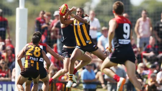 Josh Gibson of the Hawks marks the ball against Tom McDonald of the Demons during the AFL practice match between the Melbourne Demons and the Hawthorn Hawks at Casey Fields on March 8, 2014 in Melbourne, Australia.