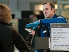A TSA officer checks a passenger's boarding pass and identification papers at Washington's Reagan National Airport.