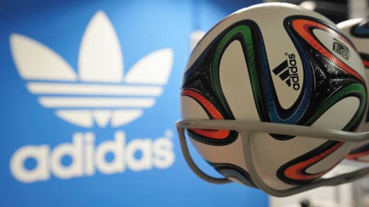 Brazuca match balls for the FIFA World Cup 2014 lie in a rack in front of the adidas logo