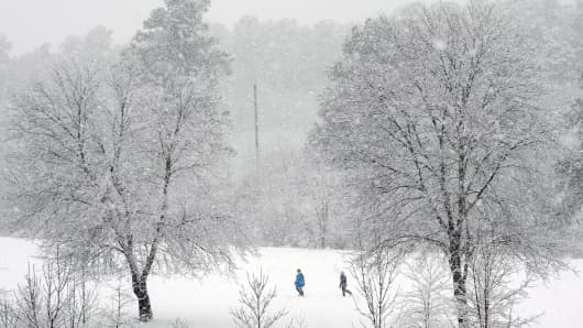 People trek through a snow covered golf course in Durham, N.C., on Feb. 13, 2014.