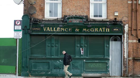 A pedestrian walks past the closed down Vallence & McGrath bar on North Wall Quay in Dublin, Ireland.