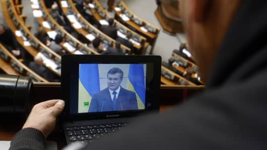 A journalist watches the televised speech of ousted Ukrainian President Viktor Yanukovych on March 11, 2014.