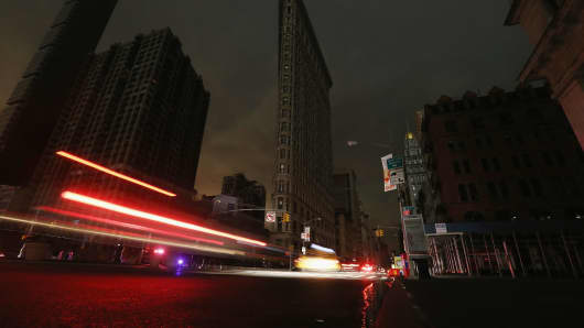 Cars are blurred as they pass by a darkened Flatiron Building in a section of Manhattan still in a blackout following Hurricane Sandy on October 30, 2012 in New York City.