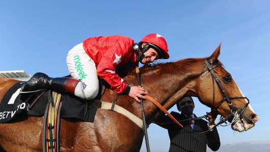 A jockey celebrates victory at Cheltenham Festival at Cheltenham Racecourse on March 12, 2014