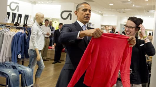 President Barack Obama holds a shirt as he shops for clothing alongside store employee Susan Panariello, during a visit to a Gap clothing store in New York City, March 11, 2014.