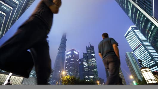 A snapshot of a megacity: Pedestrians walk in the Lujiazui district of Shanghai,  a center with a population of 25 million.