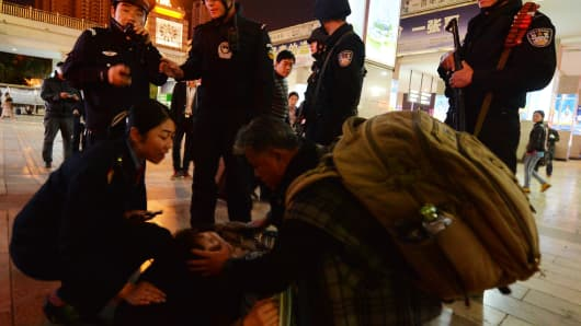 Chinese armed police and officials help a sick woman at the scene of the terror attack at the main train station in Kunming, Yunnan Province.