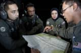 A Royal Malaysian Air Force Navigator captain Izam Fareq Hassan (R) talks with his team members onboard a Malaysian Air Force CN235 aircraft during a search and rescue (SAR) operation to find the missing Malaysia Airlines flight MH370 pla