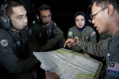 A Royal Malaysian Air Force Navigator captain Izam Fareq Hassan (R) talks with his team members onboard a Malaysian Air Force CN235 aircraft during a search and rescue (SAR) operation to find the missing Malaysia Airlines flight MH370 plane over the Strait of Malacca on March 14, 2014.