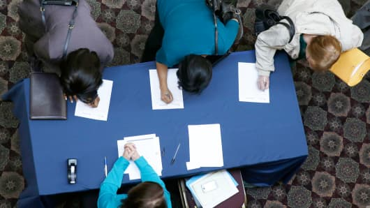In this Wednesday, Jan. 22, 2014, photo, job seekers sign in before meeting prospective employers during a career fair at a hotel in Dallas.