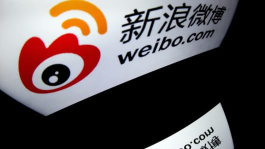 The Weibo app logo is displayed on a tablet computer