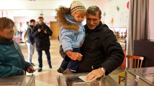 A man holds a child as he votes inside a polling station on March 16, 2014 in Perevevalne, Ukraine.