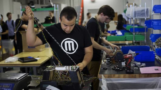 An employee assembles a Makerbot Industries LLC 3D Printer at the company's new factory in the Brooklyn borough of New York.