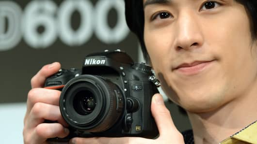 A model displays the new FX-format digital single lens reflex (SLR) camera 'D600' from Japanese camera maker Nikon during a press preview in Tokyo.