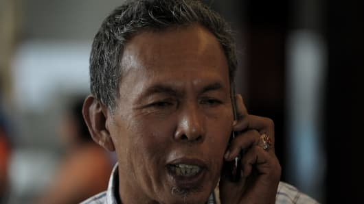 Selamat Omar, 60, the father of Mohd Khairul Amri Selamat, a 29-year-old aviation engineer who was travelling to Beijing on the missing Malaysia Airlines Boeing 777-200 plane, to work on aircraft repairs, uses his mobile phone at a hotel in Putrajaya.
