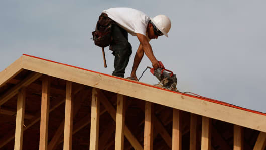 A worker uses a saw on a roof while building a new home at the Toll Brothers Inc. Baker Ranch community development in Lake Forest, California, Feb. 11, 2014.