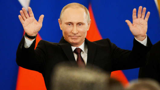 Russia's President Vladimir Putin gestures after signing a treaty on the Ukrainian Black Sea Crimea peninsula becoming part of Russia in the Kremlin in Moscow on March 18, 2014.